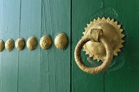 Gold painted doorknocker on a green wooden door in Asilah, Morocco Reklamní fotografie