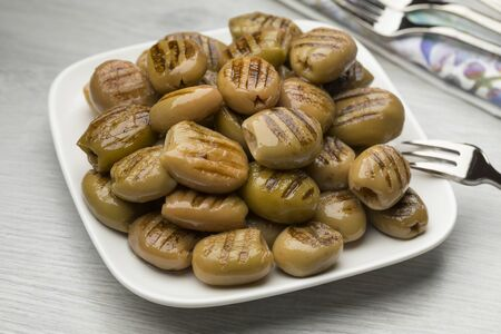 Dish with grilled green olives as a snack close up Reklamní fotografie