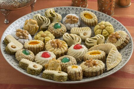 Diversity of traditional festive Moroccan cookies on a dish and tea