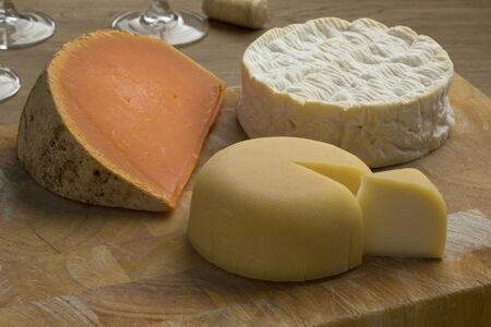 Diversity of traditional French cheese like Camembert, Mimolette and Le Mouillotin on a cutting board Фото со стока