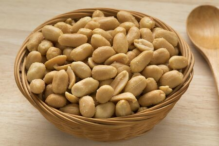 Basket with salted peanuts as a snack close up