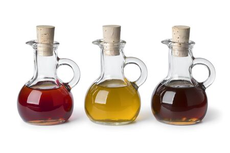 Three glass bottles with different types of cooking oil isolated on white background Фото со стока