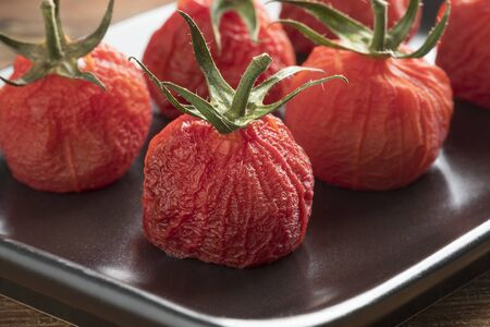 Roasted peeled red vine tomatoes with stem on a dish close up