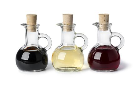 Three glass bottles with different types of vinegar isolated on white background