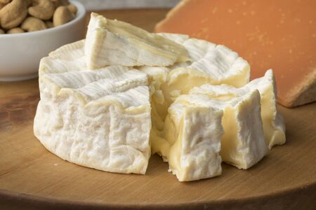 Traditional soft  French Camembert cheese and pieces close up on a cutting board Stock fotó