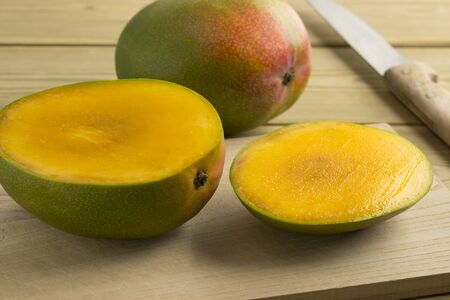 Fresh sliced mango and a whole one in the backgroundwhite background