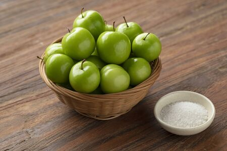 Basket with fresh green Can Erik plums and a bowl with salt Imagens