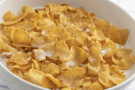 Bowl with traditional cornflakes and milk close up isolated on white background