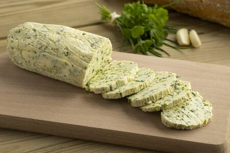Sliced fresh made herb butter close up on a cutting board