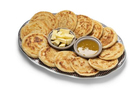 Fresh baked meloui, Moroccan pancakes with butter and honey on a plate isolated on white background