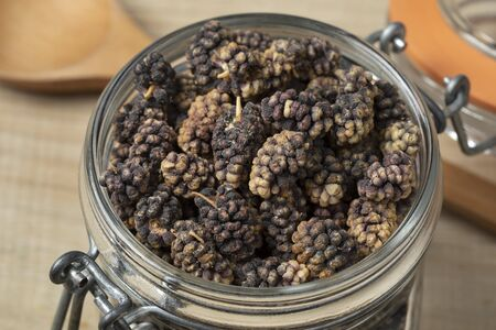 Dried black mulberries in a glass jar close up as an ingredient