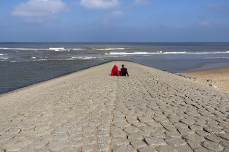 Couple looking to the North Sea sitting on the stones of a jetty at a beautiful day