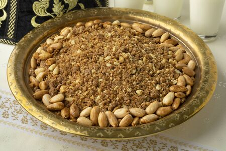 Traditional Moroccan homemade sellou on a metal dish and milk close up