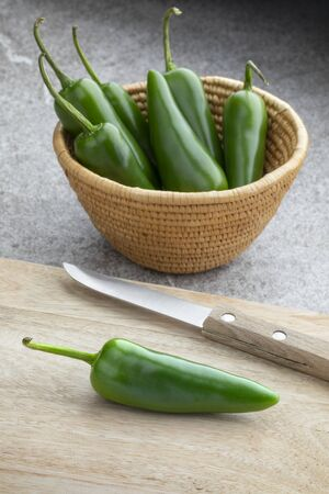 Basket with whole fresh raw green jalapeno peppers