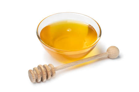Glass bowl with honey and a wooden dipper isolated on white background Фото со стока