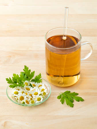 Glass of herbal tea with fresh Feverfew flowers on a dish