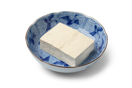 Piece of fresh white regular tofu in a Japanese bowl close up isolated on white background Фото со стока