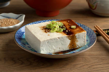 Piece of fresh white regular tofu in a Japanese bowl close up with spring onions, soy sauce and sesame seed