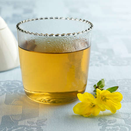 Glass cup with hot evening primrose tea and fresh yellow flowers
