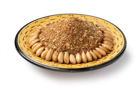Dish with traditional Moroccan homemade sellou decorated with roasted almonds isolated on white background Фото со стока