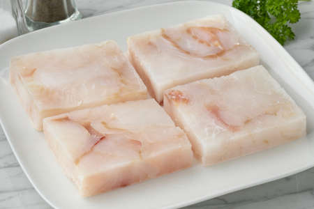 Dish with frozen cod fish fillets to thaw as an ingredient for cooking Фото со стока