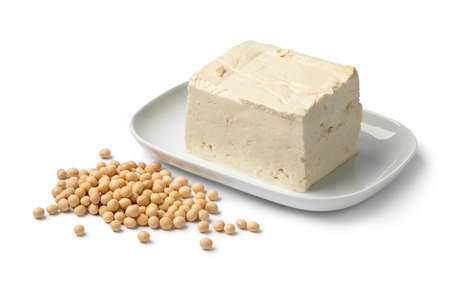 Piece of fresh firm tofu and dried soy beans close up isolated on white background Фото со стока