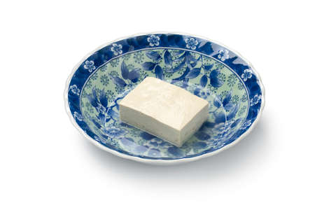 Piece of fresh white silk tofu in a Japanese bowl close up with water isolated on white background Фото со стока
