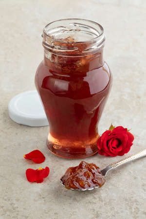 Glass jar with homemade rose petal jam and a fresh red rose Фото со стока