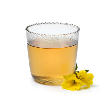 Glass cup with hot evening primrose tea and fresh yellow flowers isolated on white background