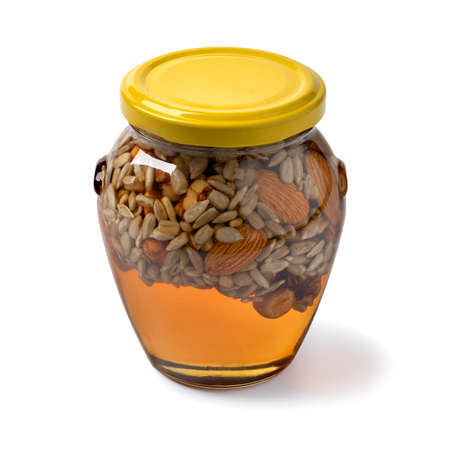 Glass jar with honey, nuts and seed isolated on white background Фото со стока