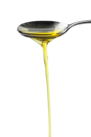 Metal spoon pouring olive oil close up Stockfoto