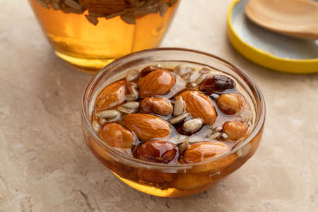 Glass jar with honey, nuts and seed close up Фото со стока