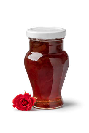 Glass jar with rose petal jam isolated on white background Фото со стока