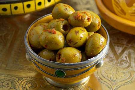 Traditional spicy green Moroccan olives in a decorative bowl as a side dish at a brass table