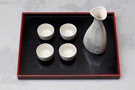 Traditional Japanese sake set with sake on a black tray