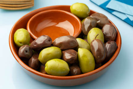 Bowl with Greek green and Kalamata olives close up for a snack