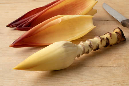 Fresh peeled raw tropical banana flower and leaves close up