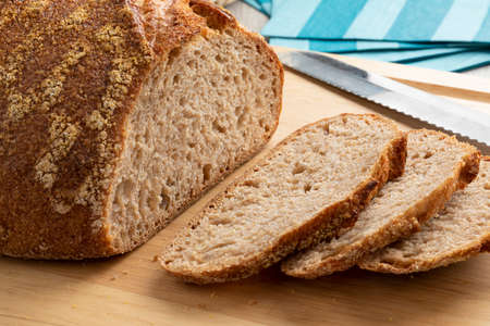 Sliced whole fresh baked German dinkel wheat bread on a cutting board close up