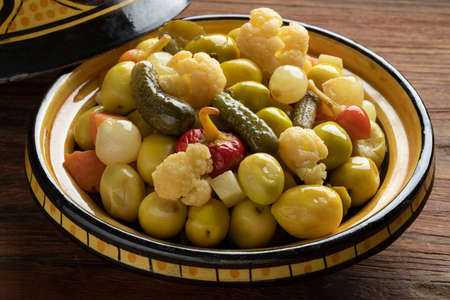 Traditional bowl with green olives and vegetables for a snack, appetizer or side dish