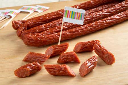 Whole and pieces of smoked polish cabanossi sausages for a snack Фото со стока
