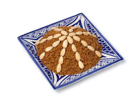 Dish with traditional Moroccan homemade sellou decorated with roasted almonds close up isolated on white background