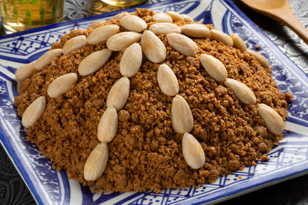 Dish with traditional Moroccan homemade sellou decorated with roasted almonds close up