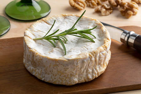 Traditional whole soft raw milk French Camembert cheese close up on a cutting board