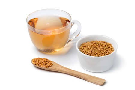 Glass cup with Fenugreek tea and a spoon and bowl with Fenugreek seeds isolated on white background