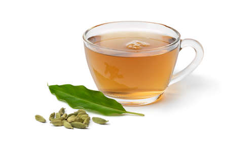 Glass cup with Cardamom tea and a heap with cardamom seeds and leaf in front isolated on white background