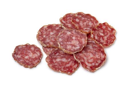 Heap of sliced Rosette de Lyon, a French pork saucisson close up isolated on white background Фото со стока