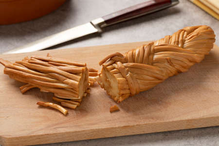 Smoked braided cheese cuttings, called Chechil, from the Adyghe Republic on a cutting board close up