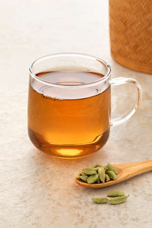 Healthy Cardamom tea with a spoon green cardamom pods in front Фото со стока