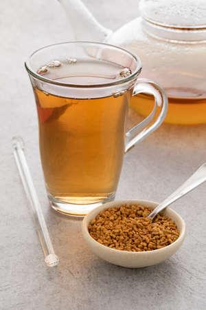 Glass cup with fresh Fenugreek tea and a bowl with Fenugreek seeds Фото со стока