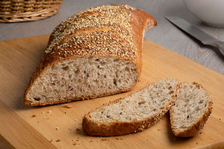 Sliced traditional sourdough loaf of bread in a special shape with seeds on a cutting board